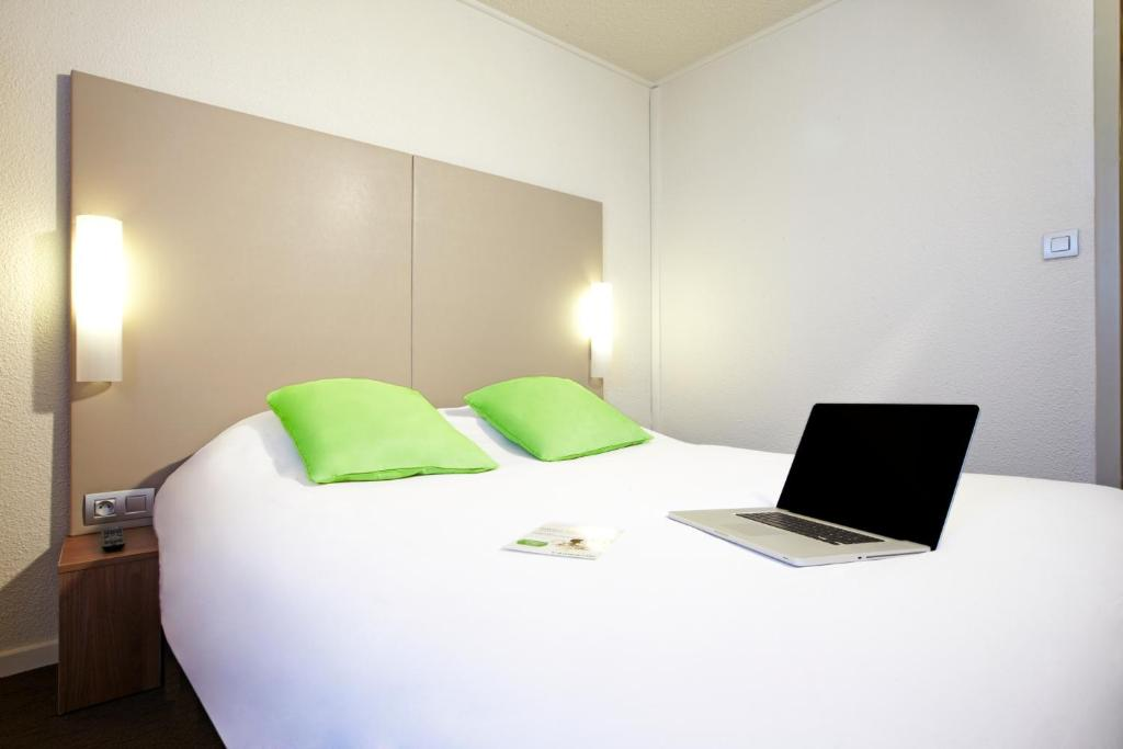 A bed or beds in a room at Campanile Nice Aéroport