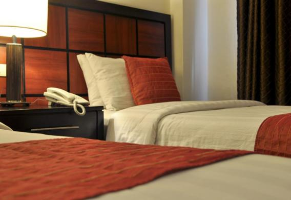 A bed or beds in a room at Sugarland Hotel
