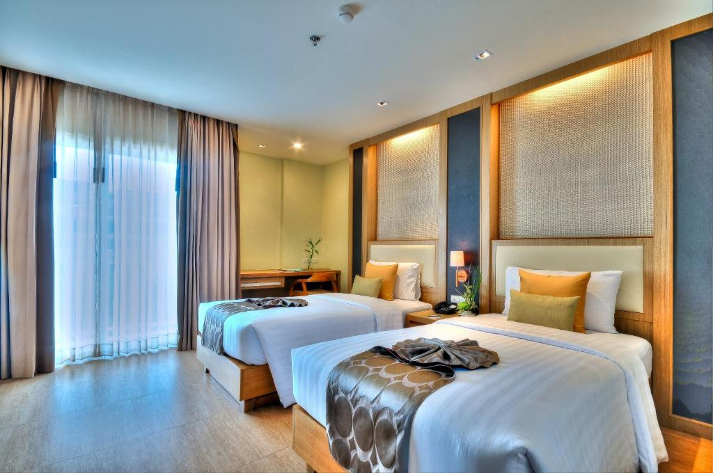A bed or beds in a room at The ASHLEE Plaza Patong Hotel & Spa