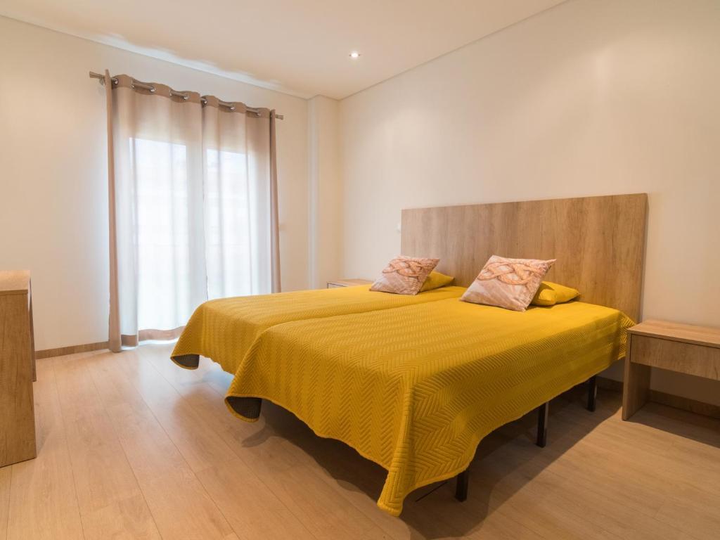 A bed or beds in a room at Luz de Fátima - Alojamentos