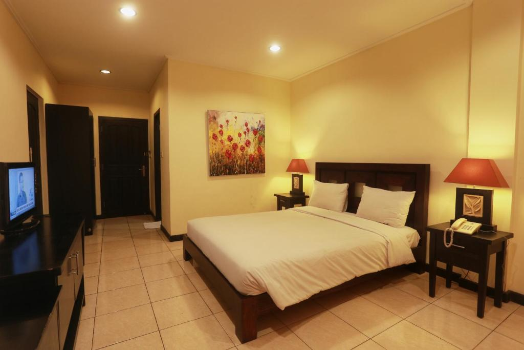 A bed or beds in a room at Hotel Intansari