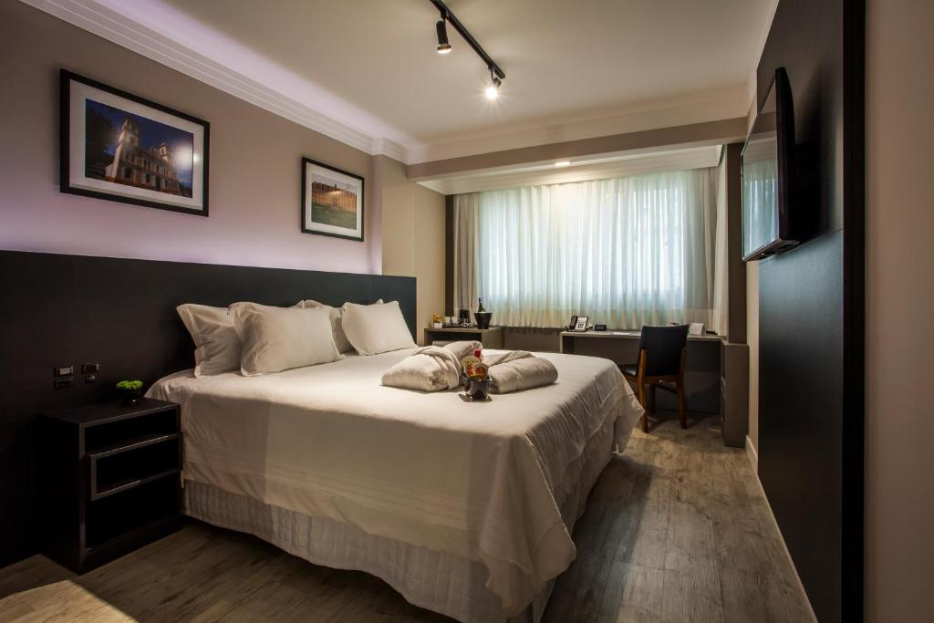 A bed or beds in a room at Santa Inn Hotel Executivo