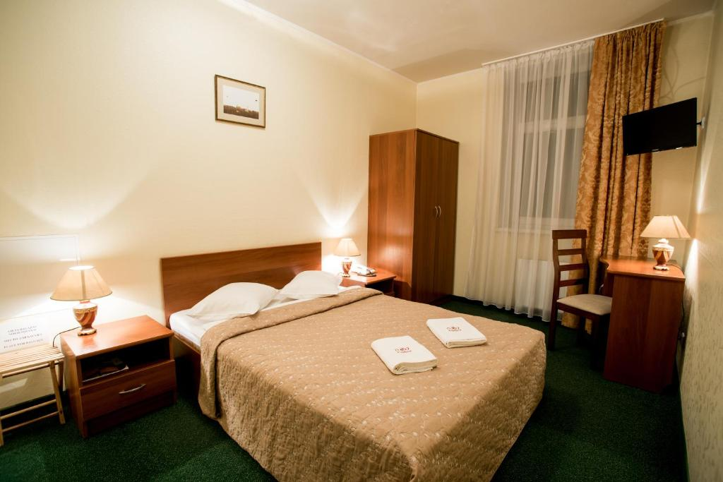 A bed or beds in a room at Good Stay Dinaburg Spa Hotel