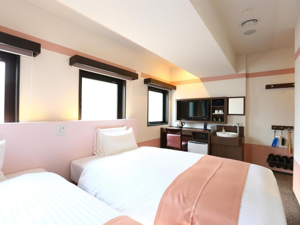 A bed or beds in a room at Hotel Wing International Select Ueno Okachimachi