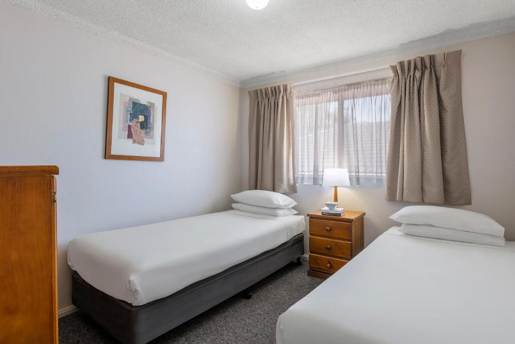 A bed or beds in a room at Waldorf North Parramatta Residential Apartments
