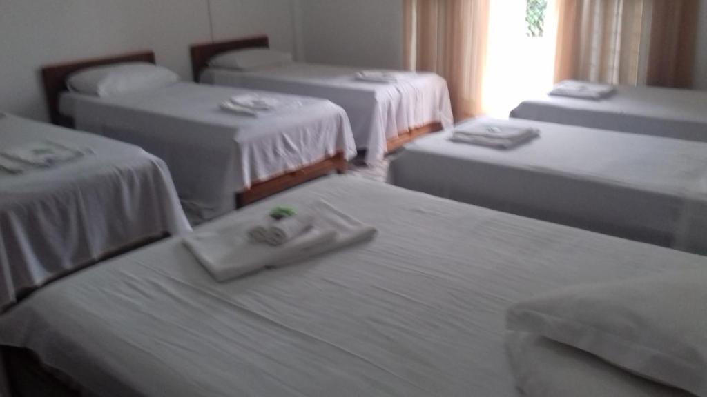 A bed or beds in a room at Pousada Oliveira