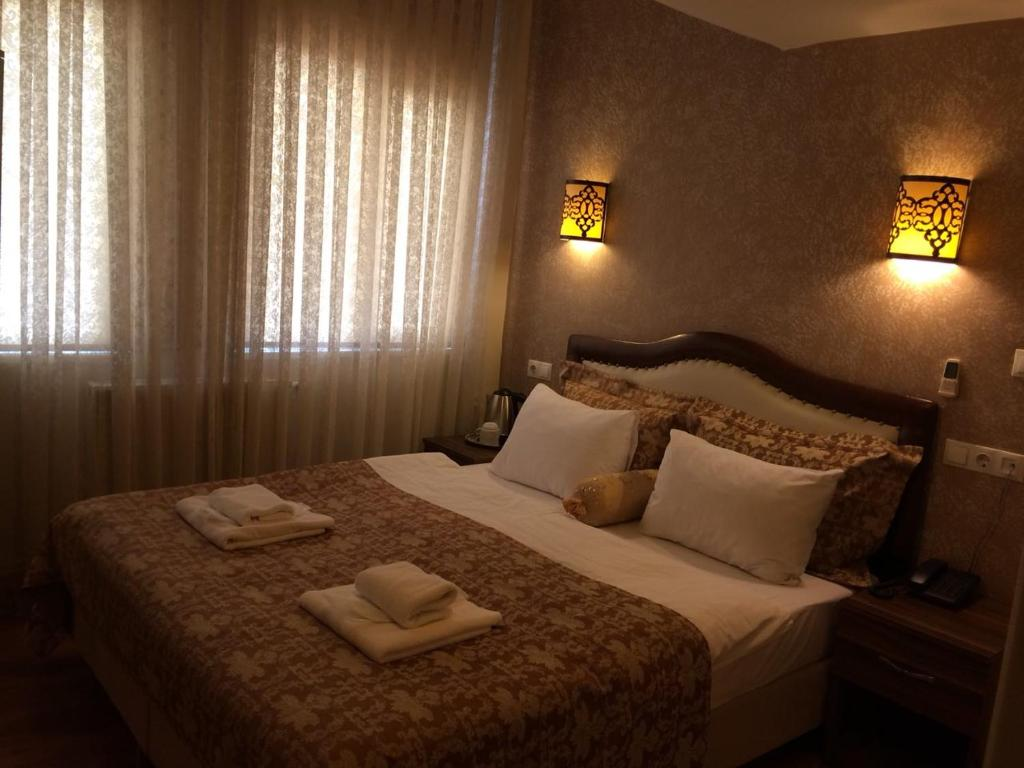 A bed or beds in a room at Hotel Buhara Family Inn