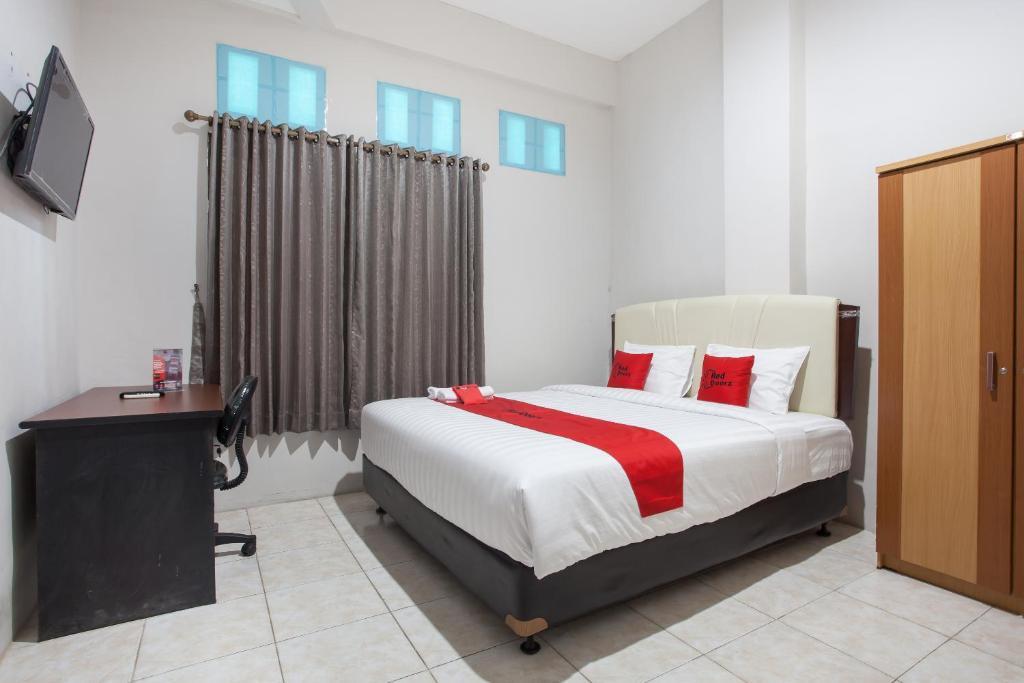 Tempat tidur dalam kamar di RedDoorz near Taman Flora