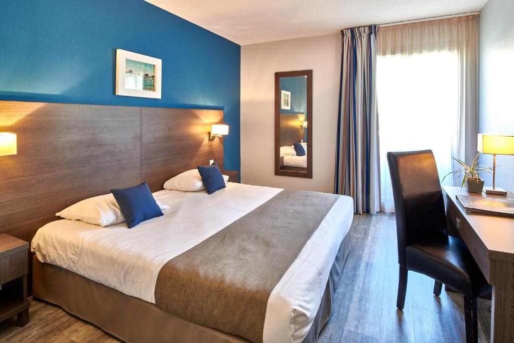 Ein Bett oder Betten in einem Zimmer der Unterkunft Hôtel Le Biarritz