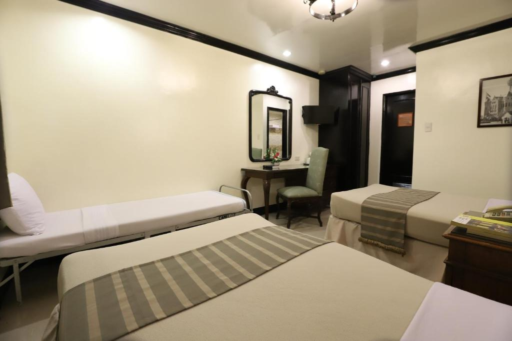 A bed or beds in a room at Camelot Hotel