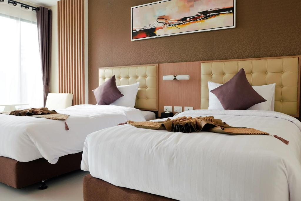 A bed or beds in a room at Hotel Ajana
