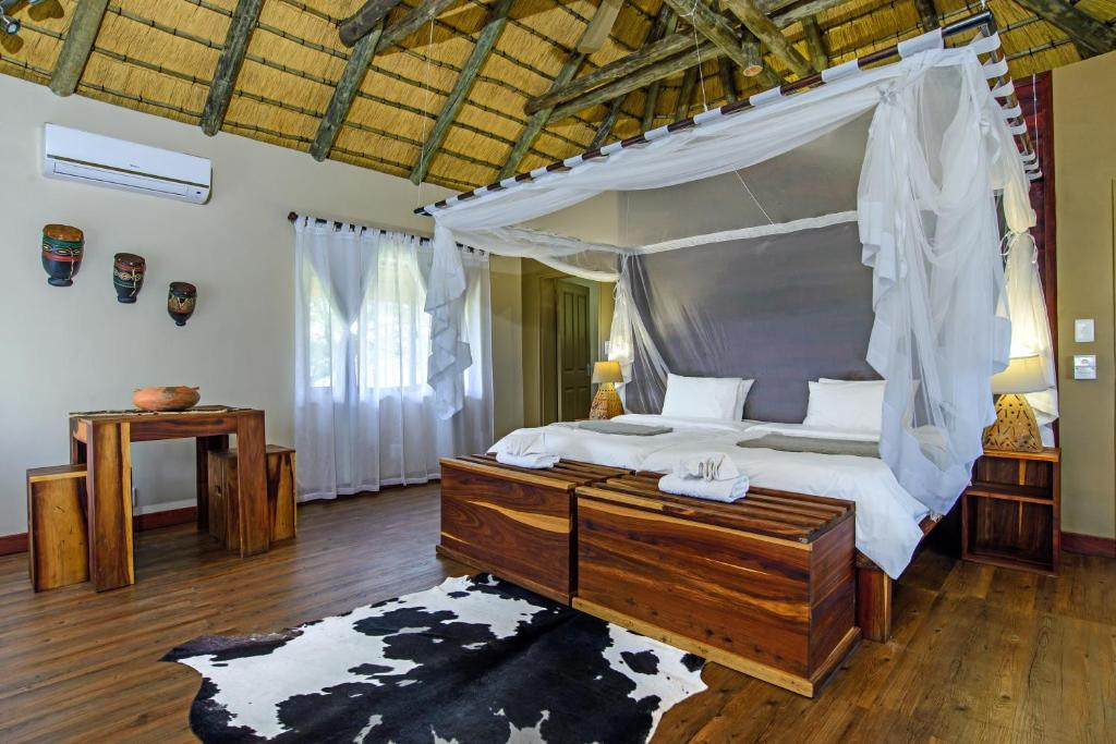 A bed or beds in a room at Gondwana Hakusembe River Lodge