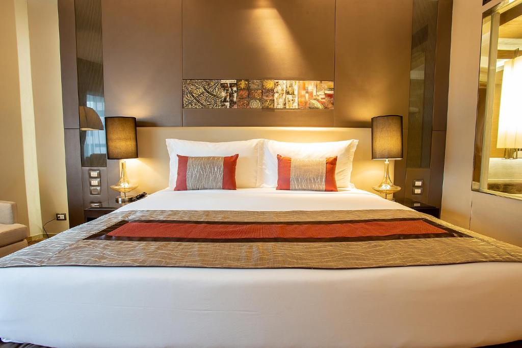 A bed or beds in a room at Graceland Bangkok by Grace Hotel