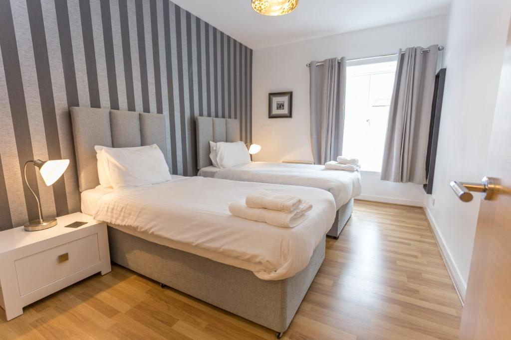 A bed or beds in a room at Aberdeen ApartHotel