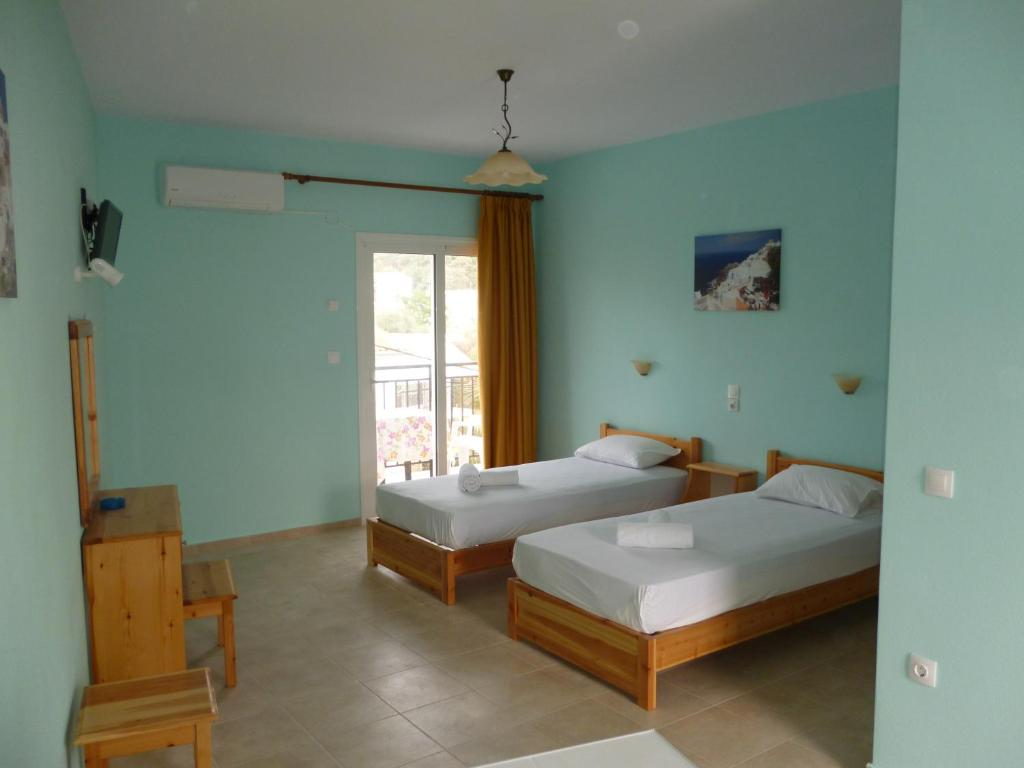 A bed or beds in a room at Alexandros Guest House