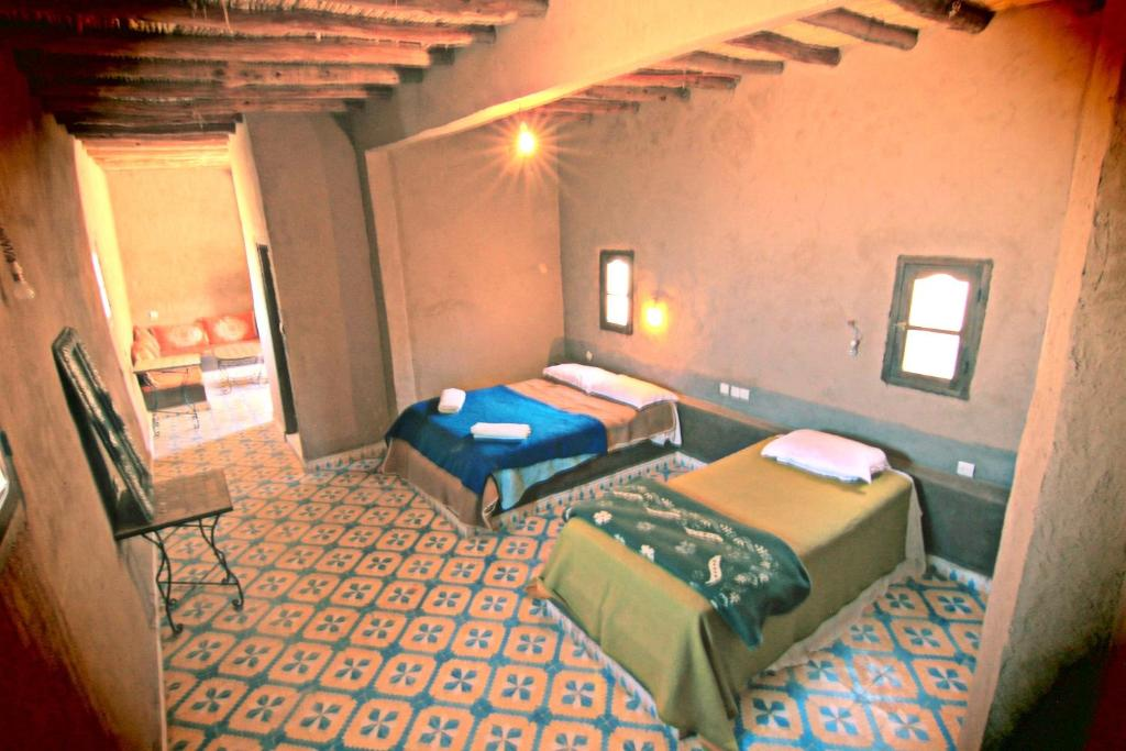 A bed or beds in a room at Maison Adrar Merzouga