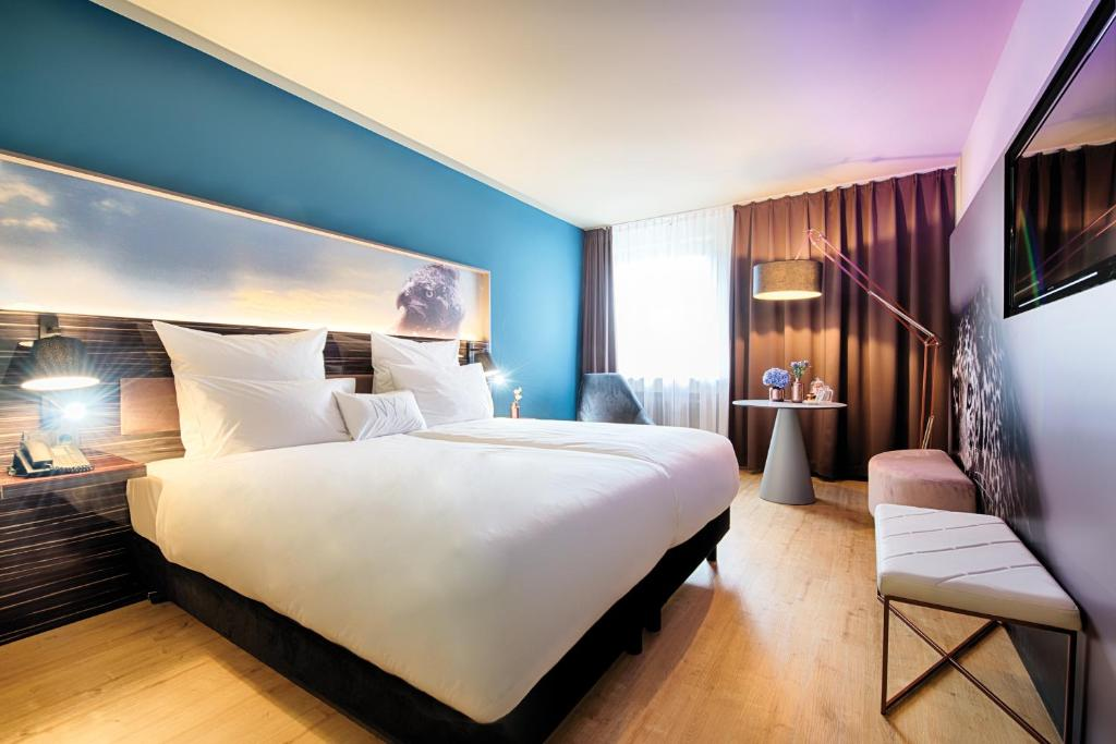 A bed or beds in a room at NYX Hotel Mannheim by Leonardo Hotels