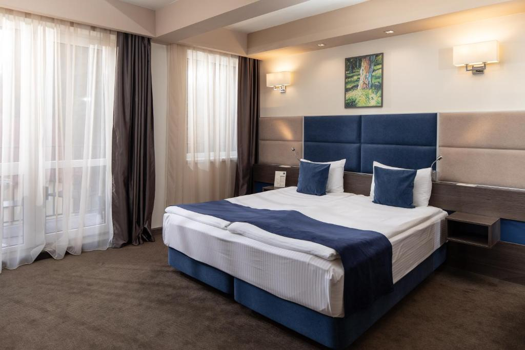 A bed or beds in a room at Belfort Hotel