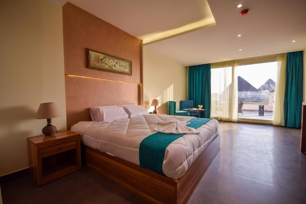 A bed or beds in a room at Pyramids Eyes Hotel