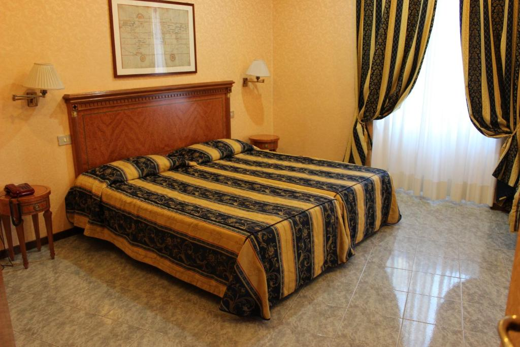 A bed or beds in a room at Dependance Hotel Dei Consoli