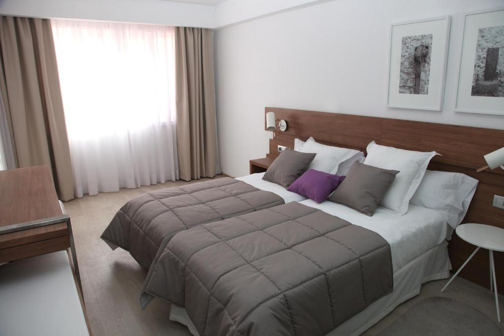 A bed or beds in a room at Hotel Gelmírez