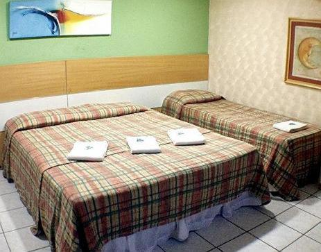 A bed or beds in a room at Raio de Sol Praia Hotel