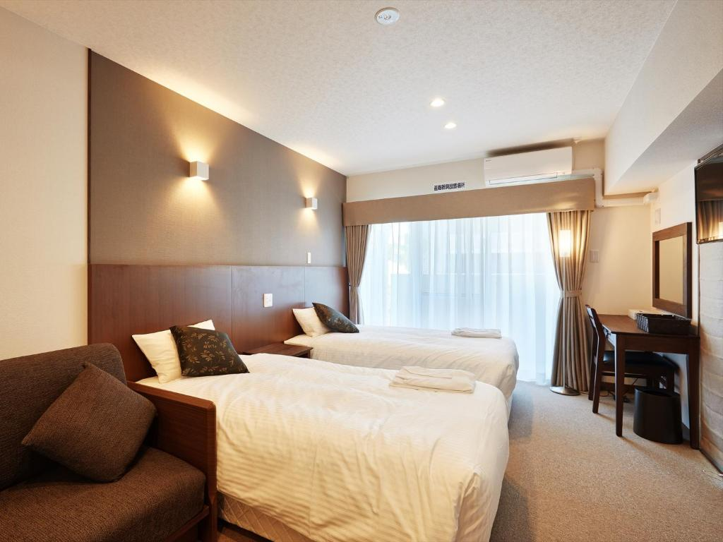 A bed or beds in a room at Creass Hotel Tsubogawa Marche