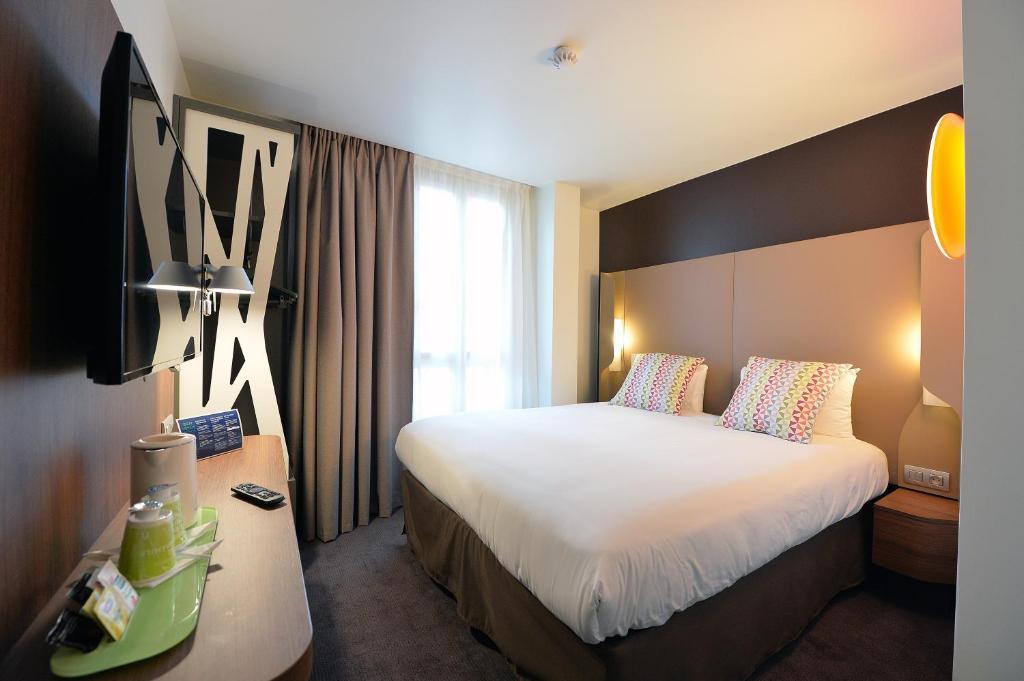 Кровать или кровати в номере CAMPANILE PARIS - Clichy Centre