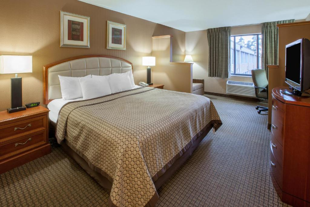 A bed or beds in a room at Days Inn & Suites by Wyndham Richfield
