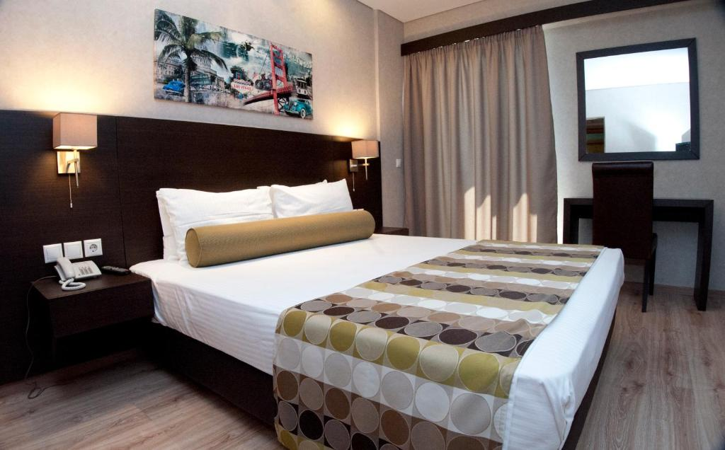A bed or beds in a room at Nefeli Hotel Alimos