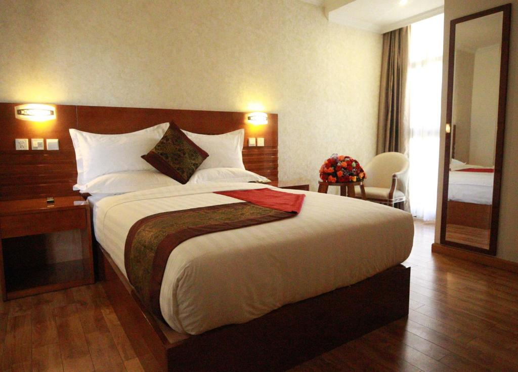 A bed or beds in a room at Marcen Addis Hotel