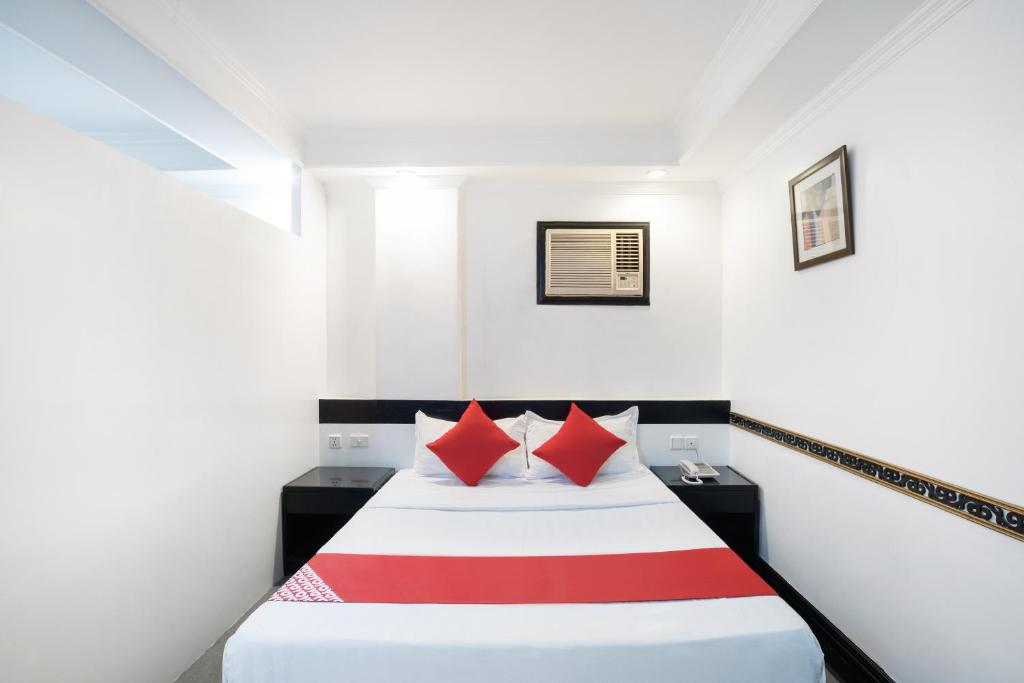 A bed or beds in a room at OYO 138 White Palace Hotel
