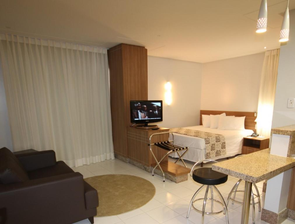 A television and/or entertainment center at Vivence Suítes Hotel Goiânia