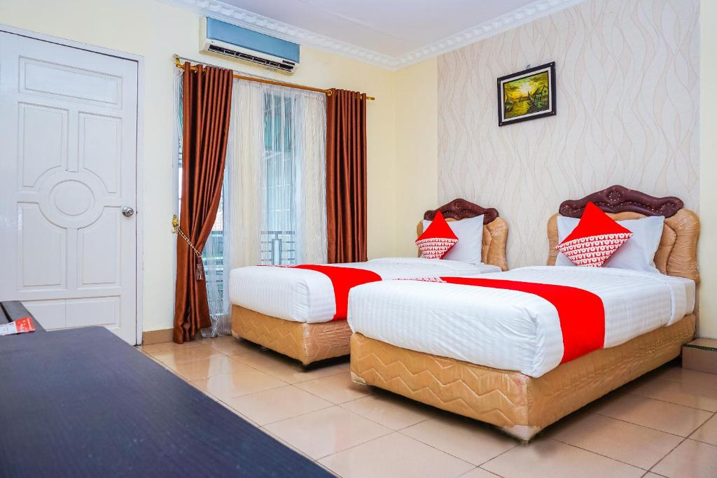 A bed or beds in a room at OYO 362 Hotel Siti Nurbaya
