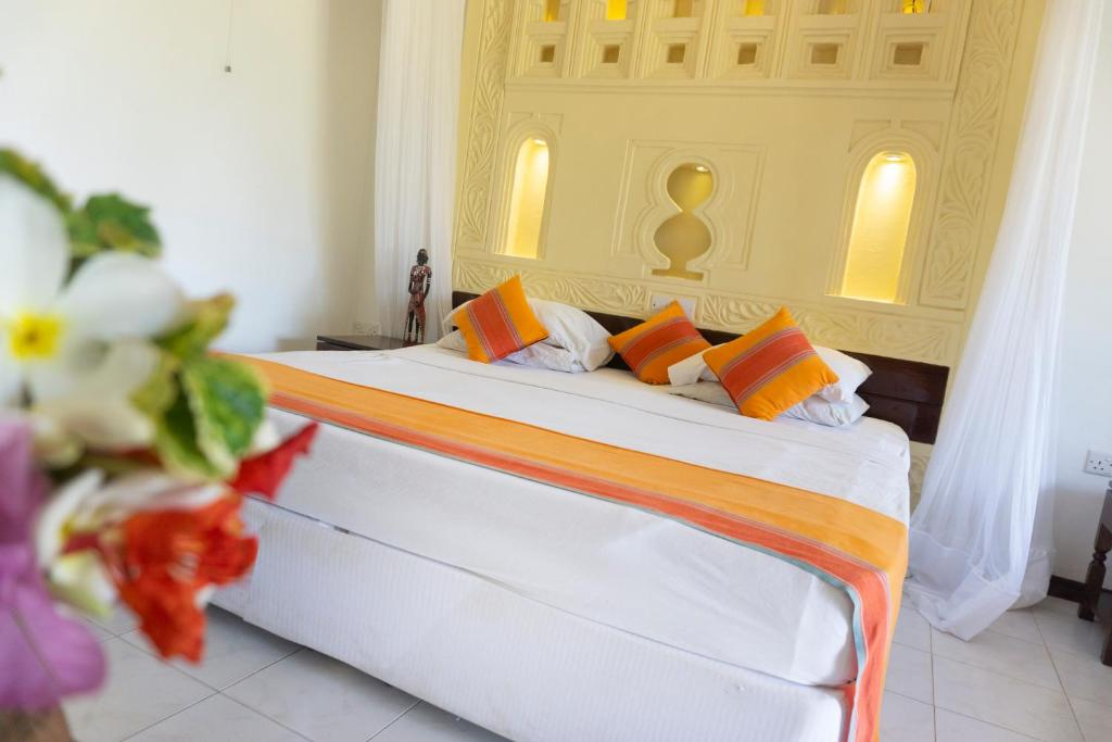 A bed or beds in a room at Reef Hotel Mombasa