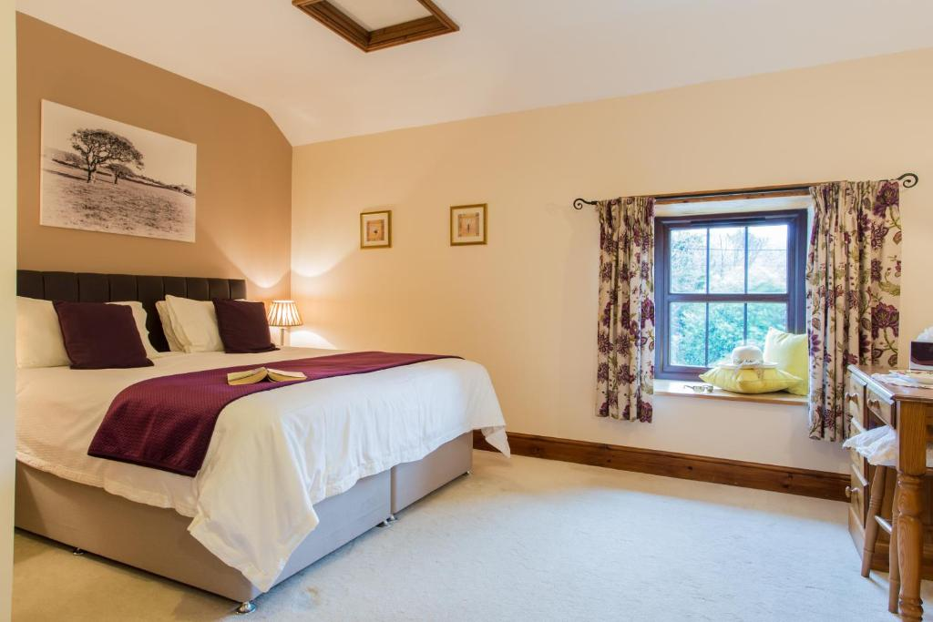A bed or beds in a room at Callestock Courtyard Cottages