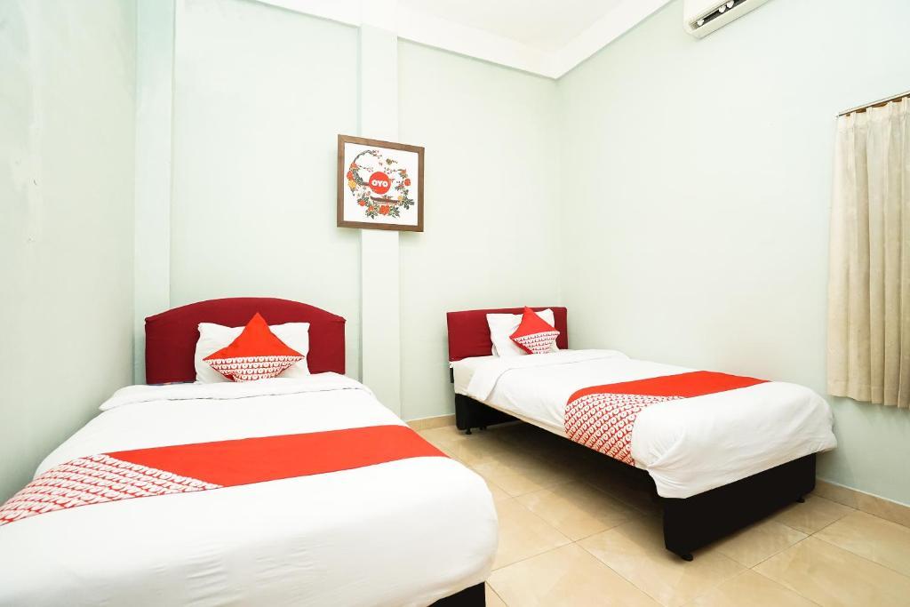 Tempat tidur dalam kamar di OYO 475 Kartika Syariah Residence