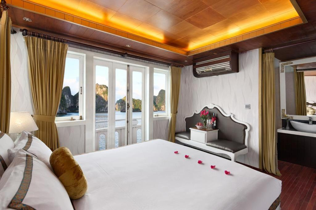 A bed or beds in a room at Majestic Halong Cruise