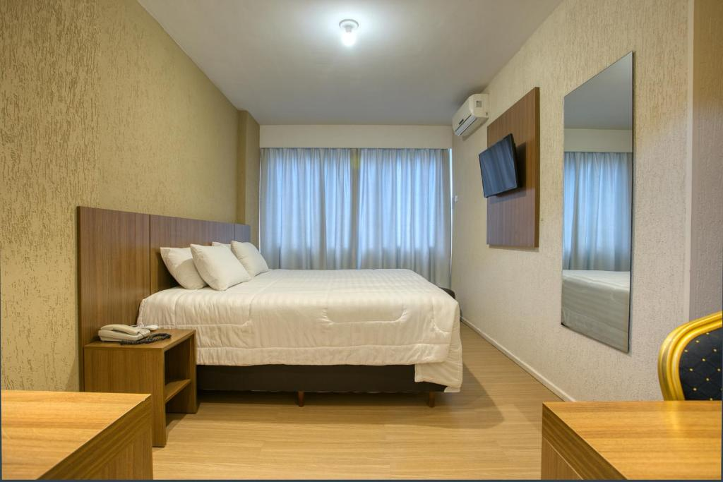 A bed or beds in a room at Roochelle Corporate Hotel