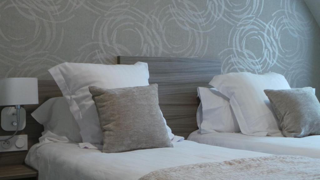 A bed or beds in a room at Hôtel De Brunville Et Restaurant Le Café Louis
