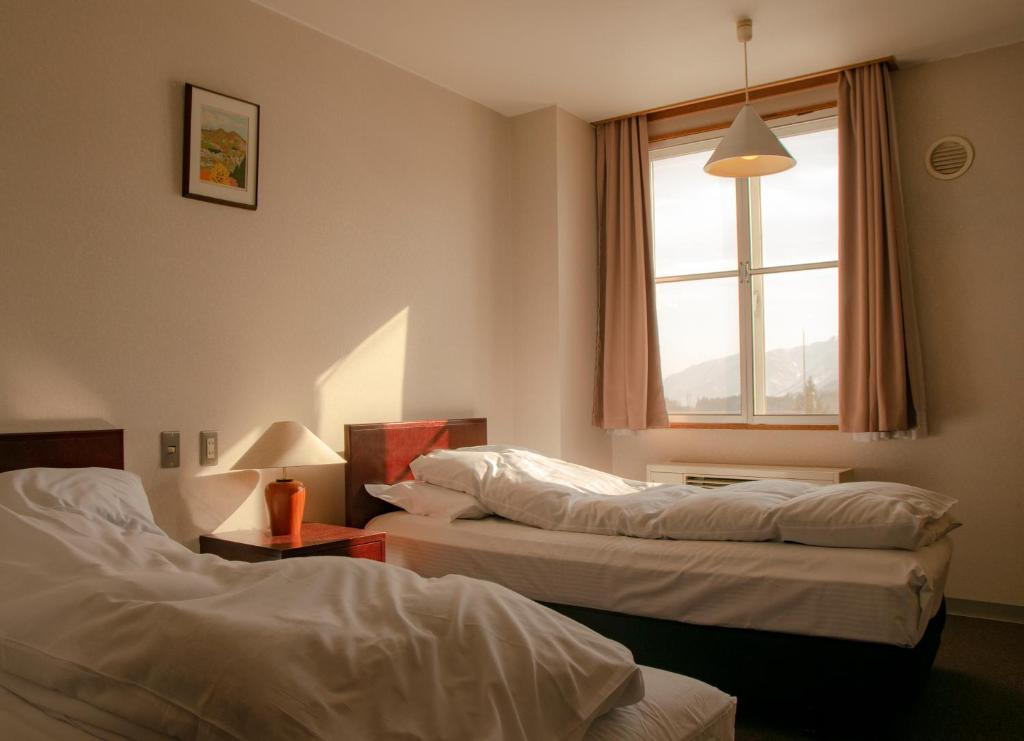 A bed or beds in a room at La Vista Hotel - Stay on the Slopes