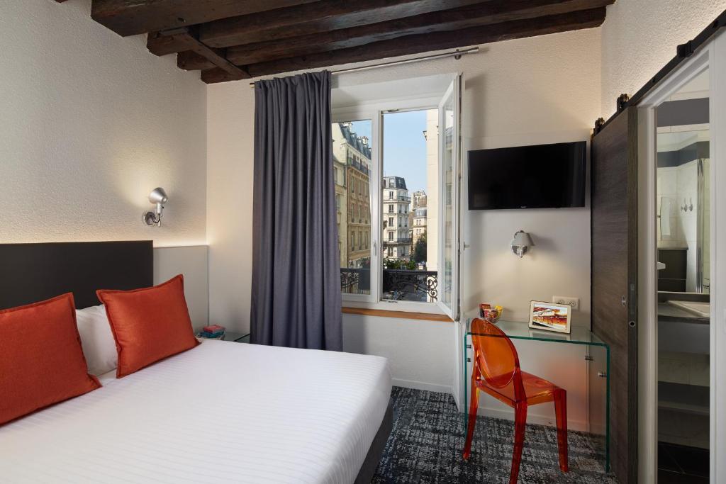 A bed or beds in a room at 3H Paris Marais Hôtel