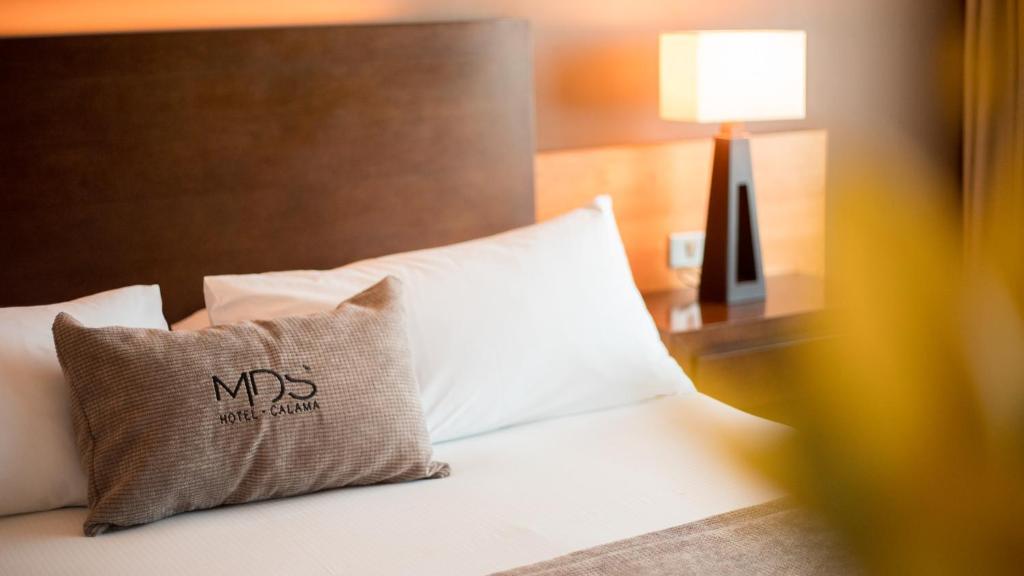 Säng eller sängar i ett rum på MDS Hotel Calama