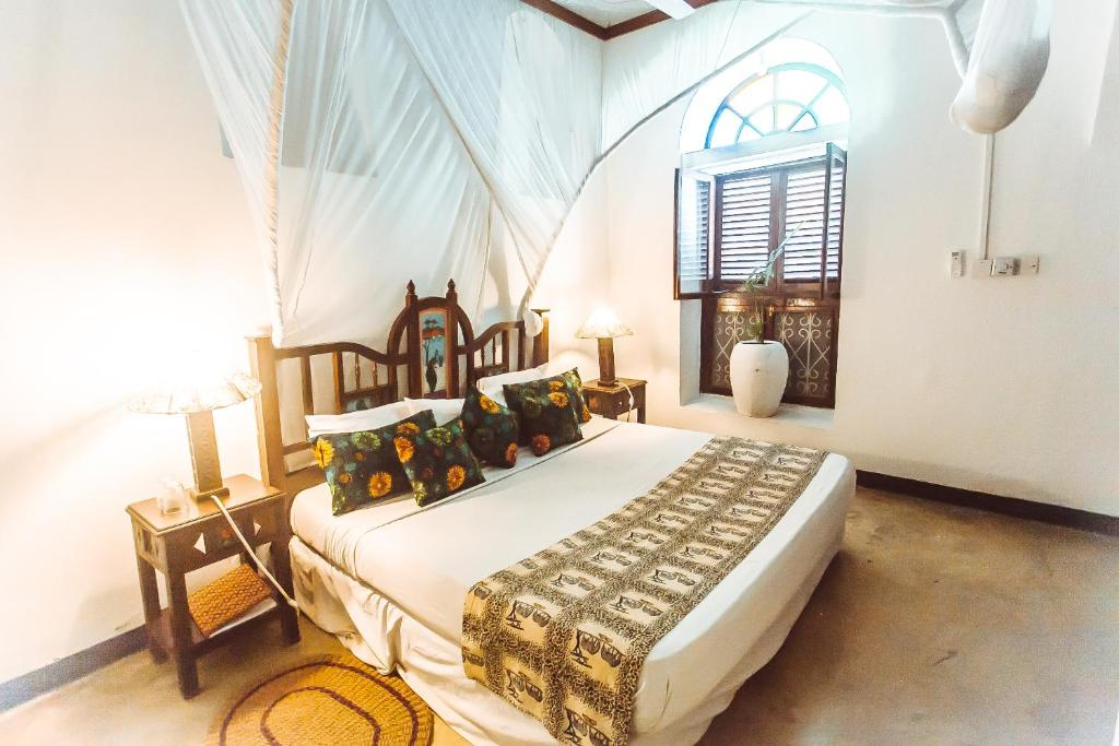 A bed or beds in a room at The Swahili House