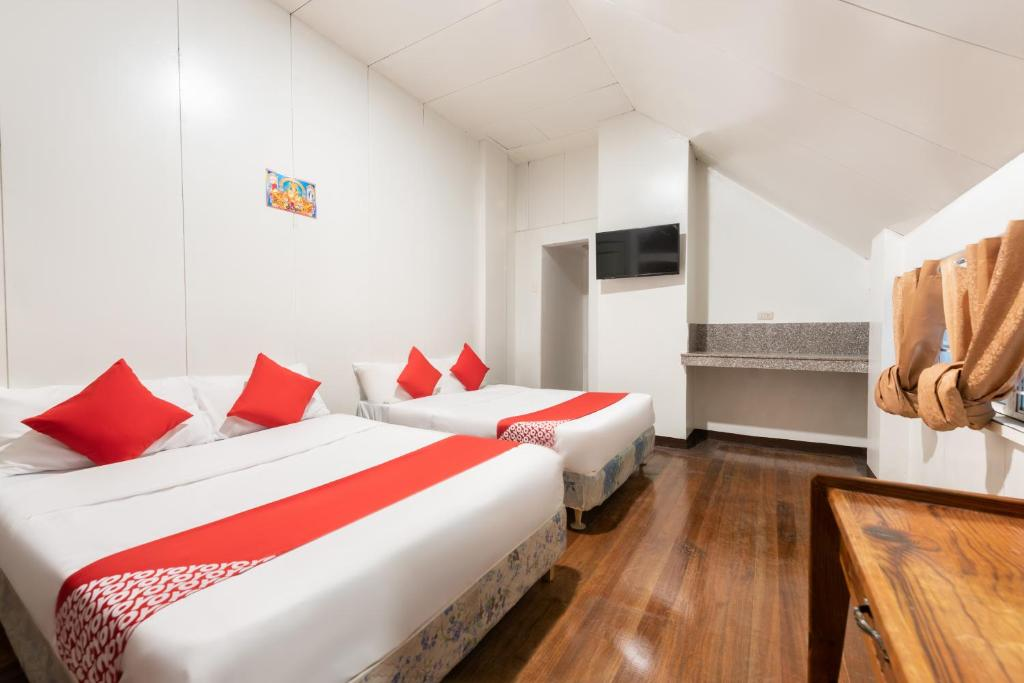 A bed or beds in a room at OYO 122 The Peak Pines Pension