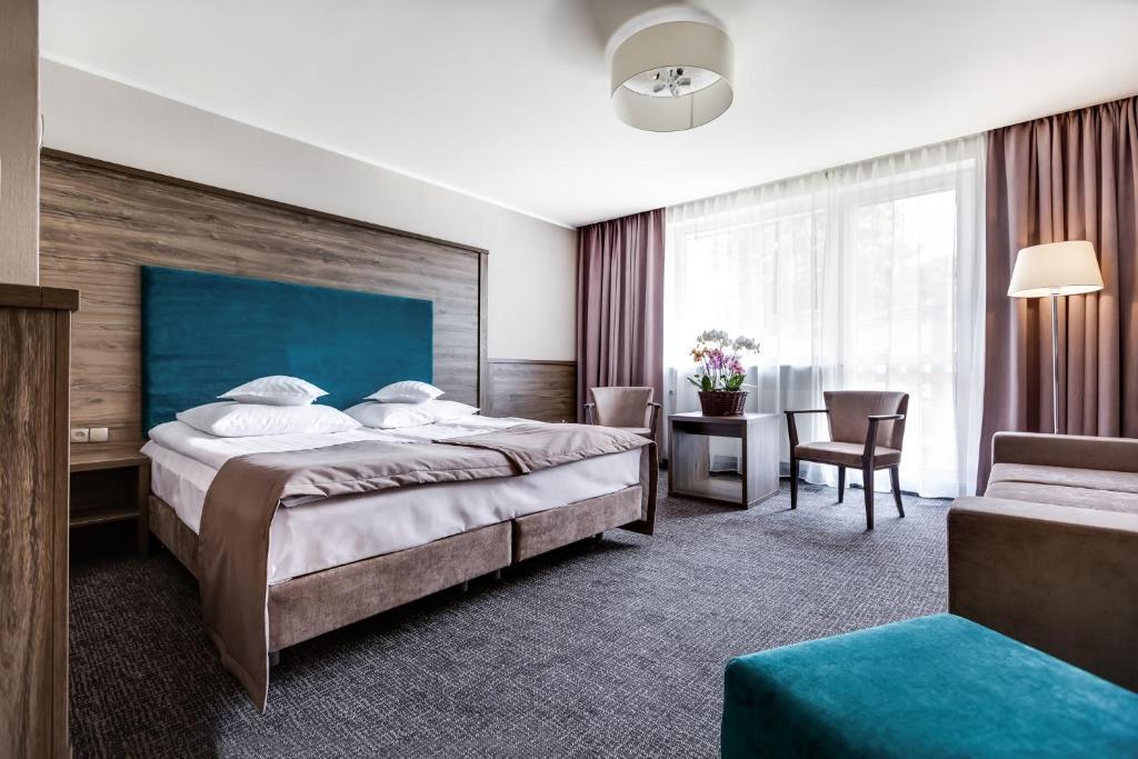 A bed or beds in a room at Hotel Konradówka