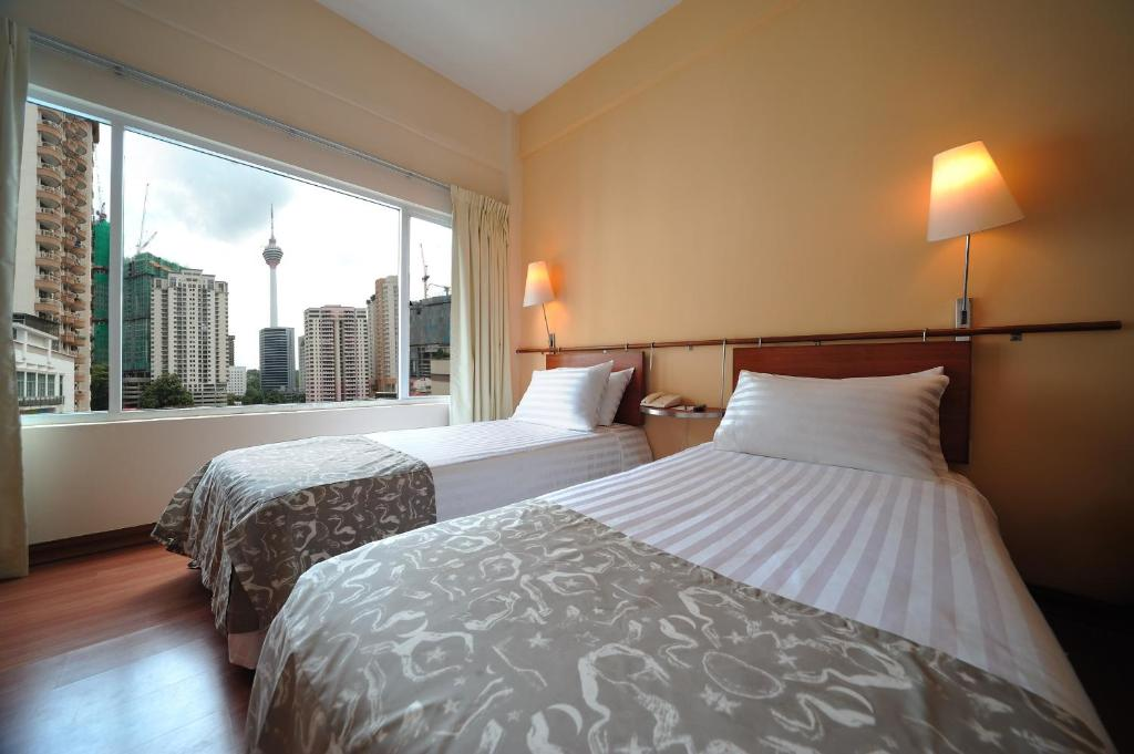 A bed or beds in a room at Alpha Genesis Hotel Bukit Bintang