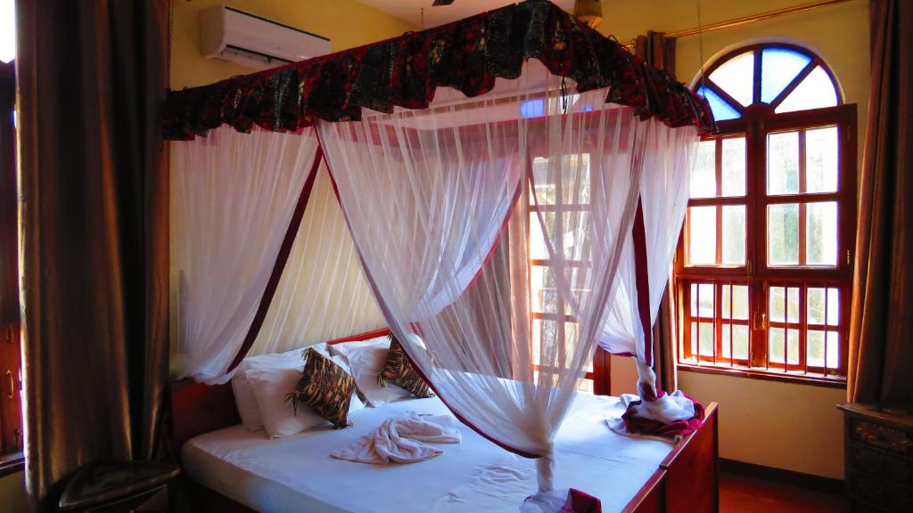 A bed or beds in a room at Rumaisa Hotel