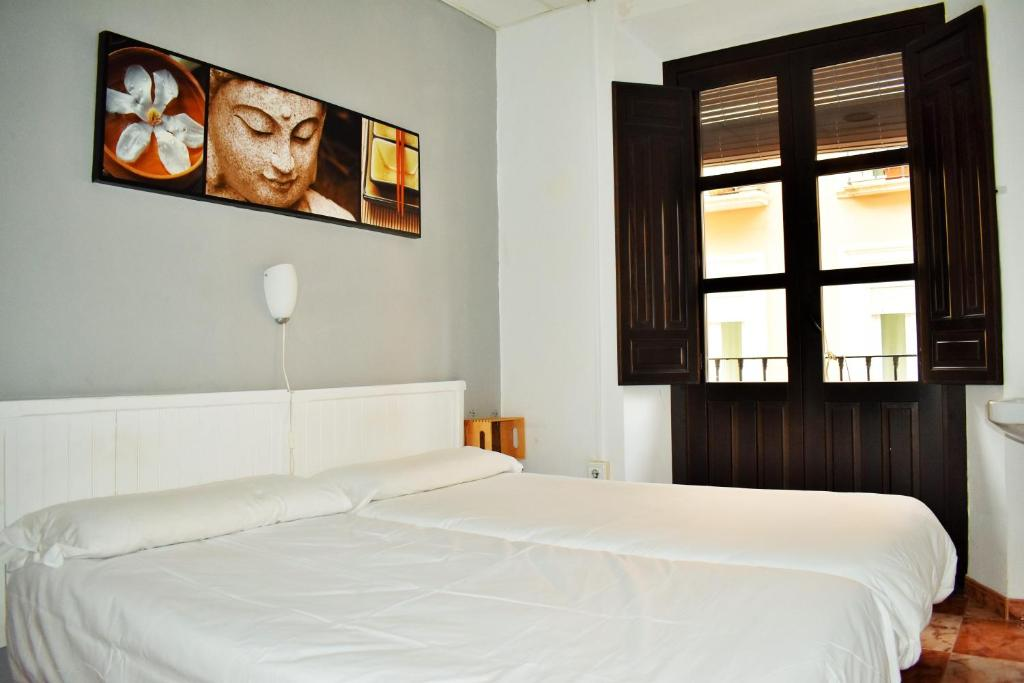 A bed or beds in a room at Pension Castil