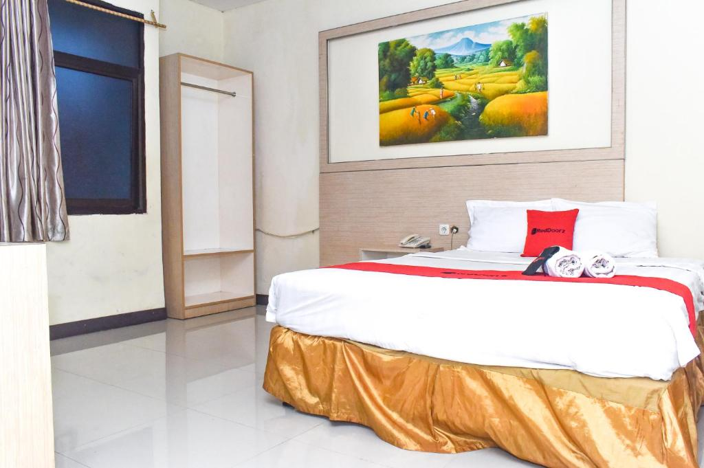A bed or beds in a room at RedDoorz Plus near Sultan Hasanuddin Airport